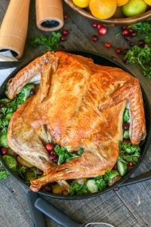 Roasted turkey in a pan with herbs around it