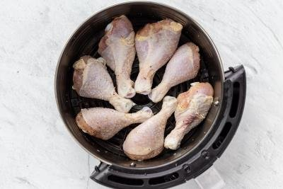 chicken legs in an air fryer basket
