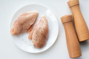 Chicken breast on a plate with salt and pepper