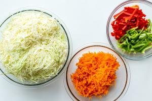 cabbage, carrots and peppers in bowls