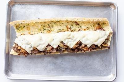 Opened steak sandwich on a baking sheet