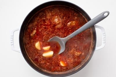 Potatoes added to a pot with borscht