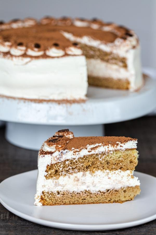 A slice of Tiramisu on a plate with a cake behind it