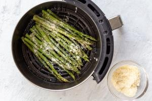 raw asparagus with parmesan in an air fryer basket