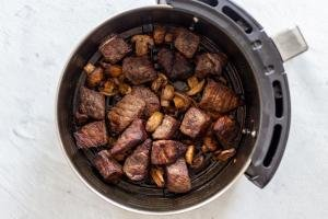 steak bites with mushrooms in an air fryer basket