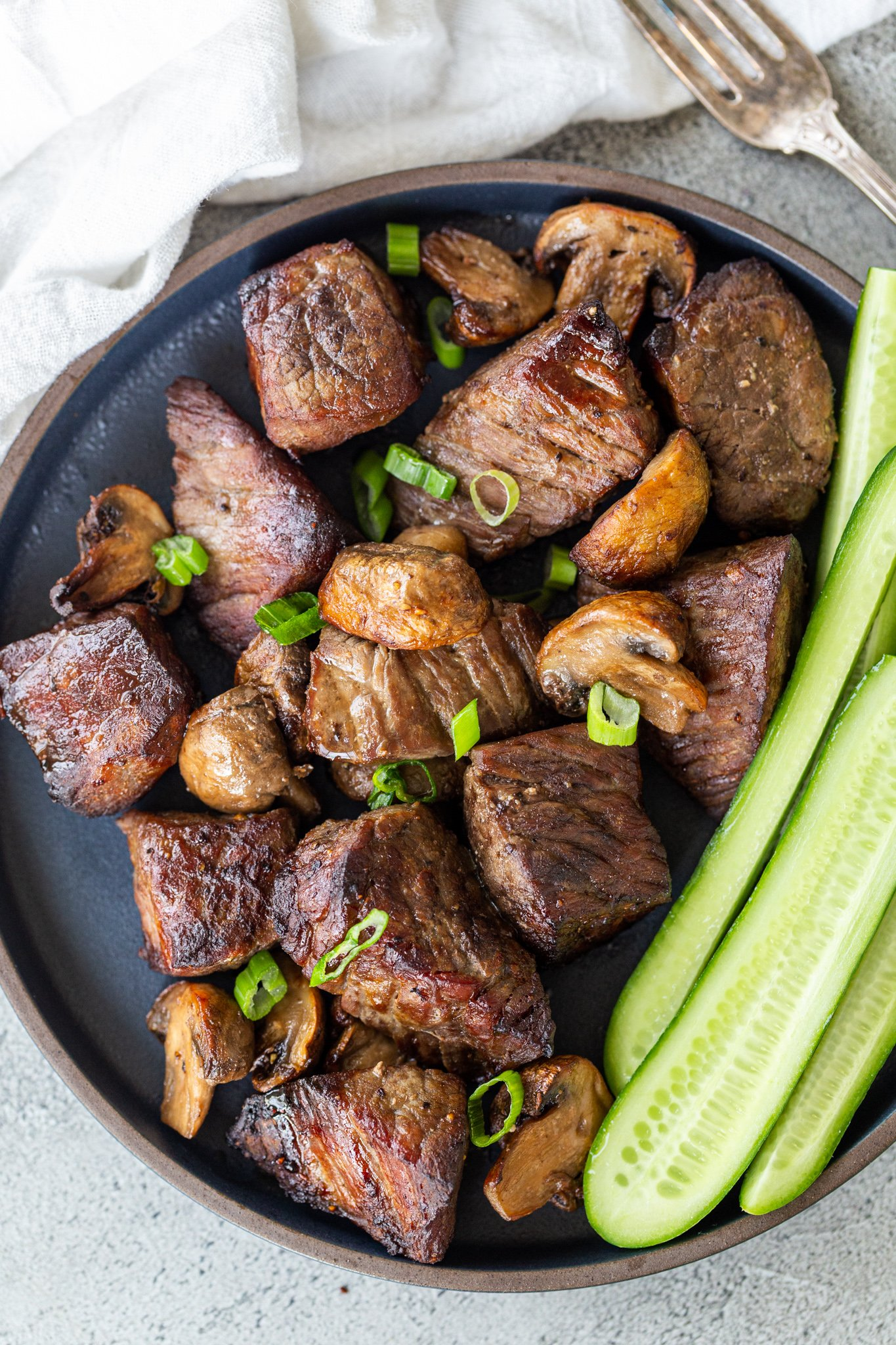 Air fryer steak bites in on a plate with cucumbers