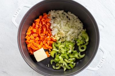 a pot with carrots, celery, onion, butter and garlic