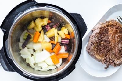 Instant pot with veggies and browned beef next to it
