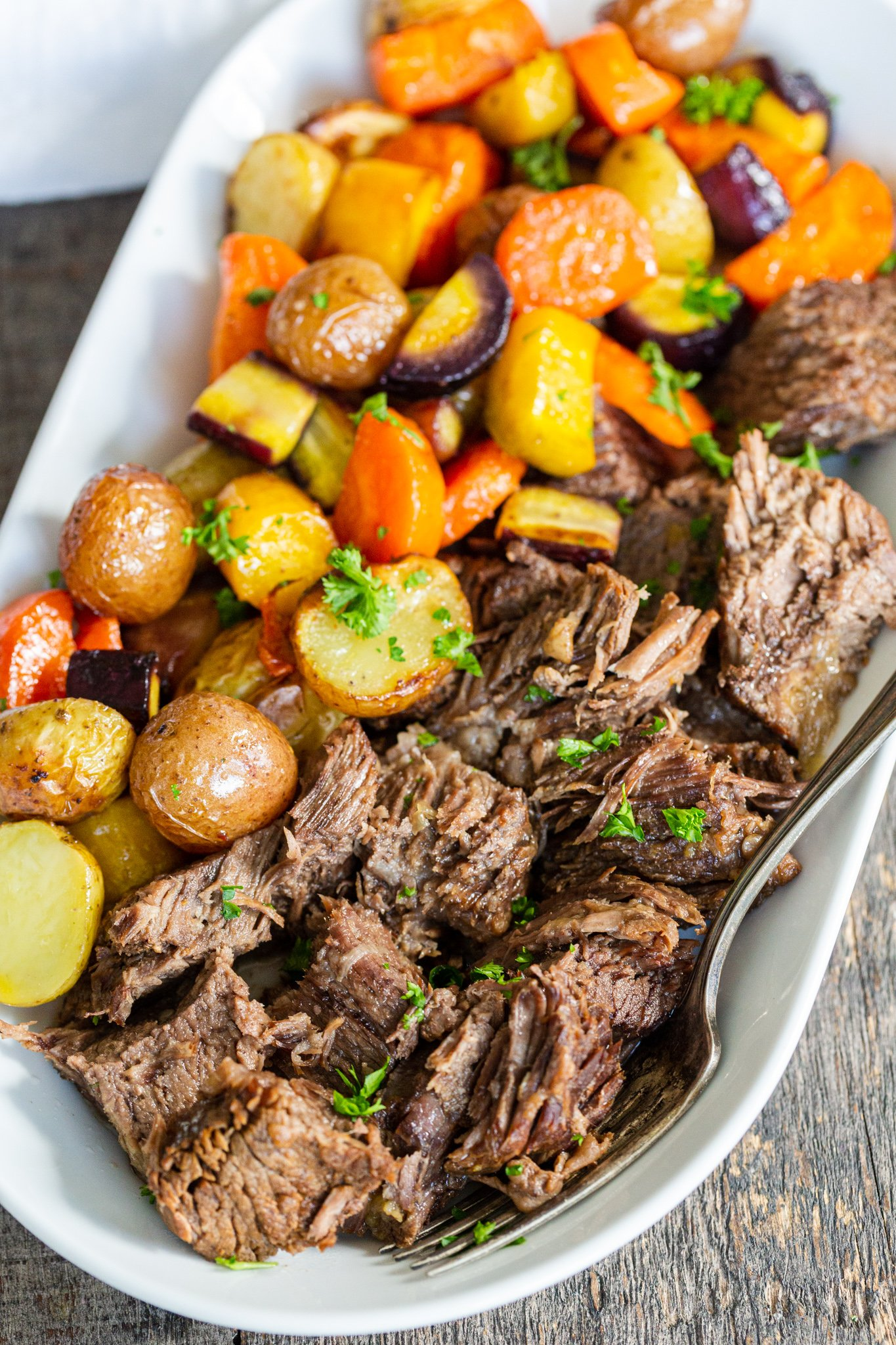 a serving plate with beef and carrots with potatoes