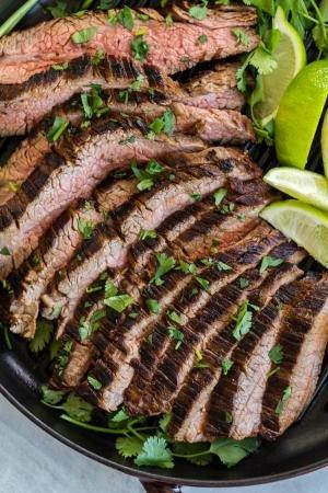 Sliced carne asada on the grilling pan