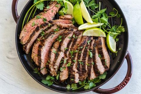 Sliced carne asada on the grilling pan with cilantro