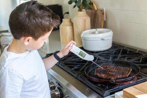 a boy checking temperature of the meat