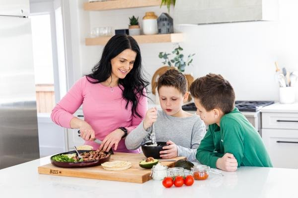 mom and two kids cooking together