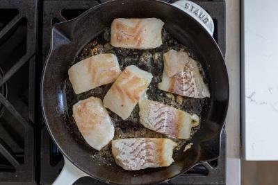 cod in a frying pan with butter
