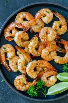 Air Fryer shrimp on a plate with herbs