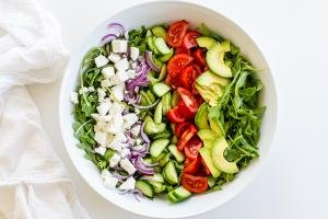veggies and cheese in a bowl for the Arugula avocado tomato and cucumber salad