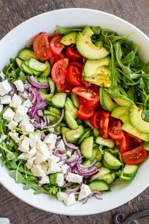 All the ingredients for Arugula avocado tomato and cucumber salad are lined up in a bowl