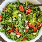 Arugula avocado tomato and cucumber salad in a bowl