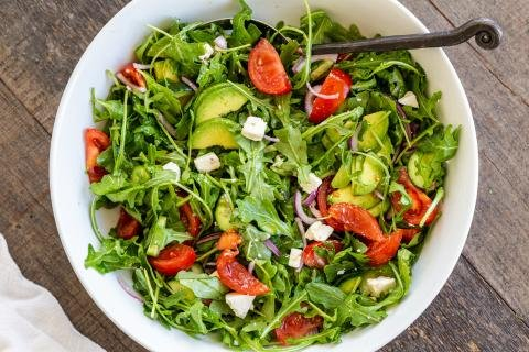 Arugula avocado tomato and cucumber salad in a bowl