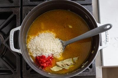broth and rice and in a pot with tomato paste and bay leaves