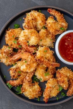 crispy air fryer coconut shrimp on a plate with a sauce