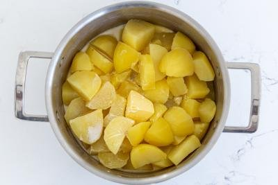 A cooking pot with potatoes and cream