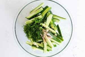 cucumbers in a bowl with dill and garlic and salt