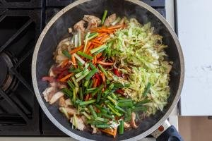 vegetables, sauce and chicken in a skillet