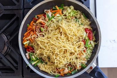 noodles in a skillet with veggies and chicken