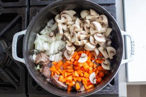 veggies and mushrooms added to the pot with beef