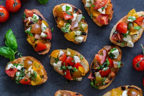 Bruschetta on a tray with tomatoes and basil