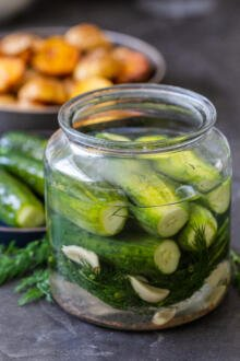 Quick pickled cucumbers in a jar with other pickles on a plate