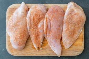 seasoned chicken breast on a cutting board
