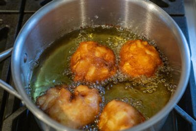 apple fritters in a pot with oil