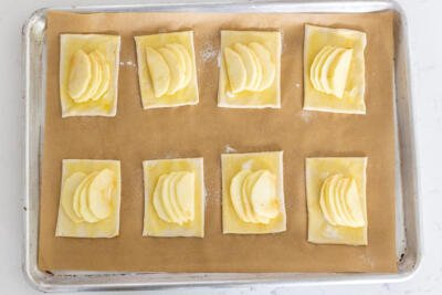 Raw apple tarts on a baking sheet