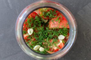 tomatoes and herbs in a jar