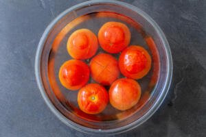 Tomatoes in a bowl with boiled water