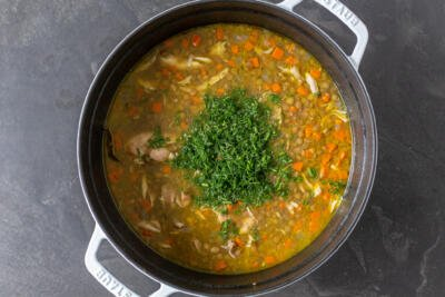 Chicken lentil soup in a pot with dill