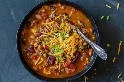 Instant Pot chili in a bowl with cheese and green onions