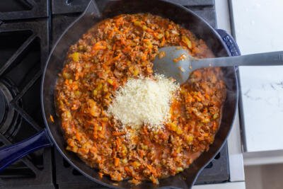 Beef Bolognese in a pan with parmesan cheese