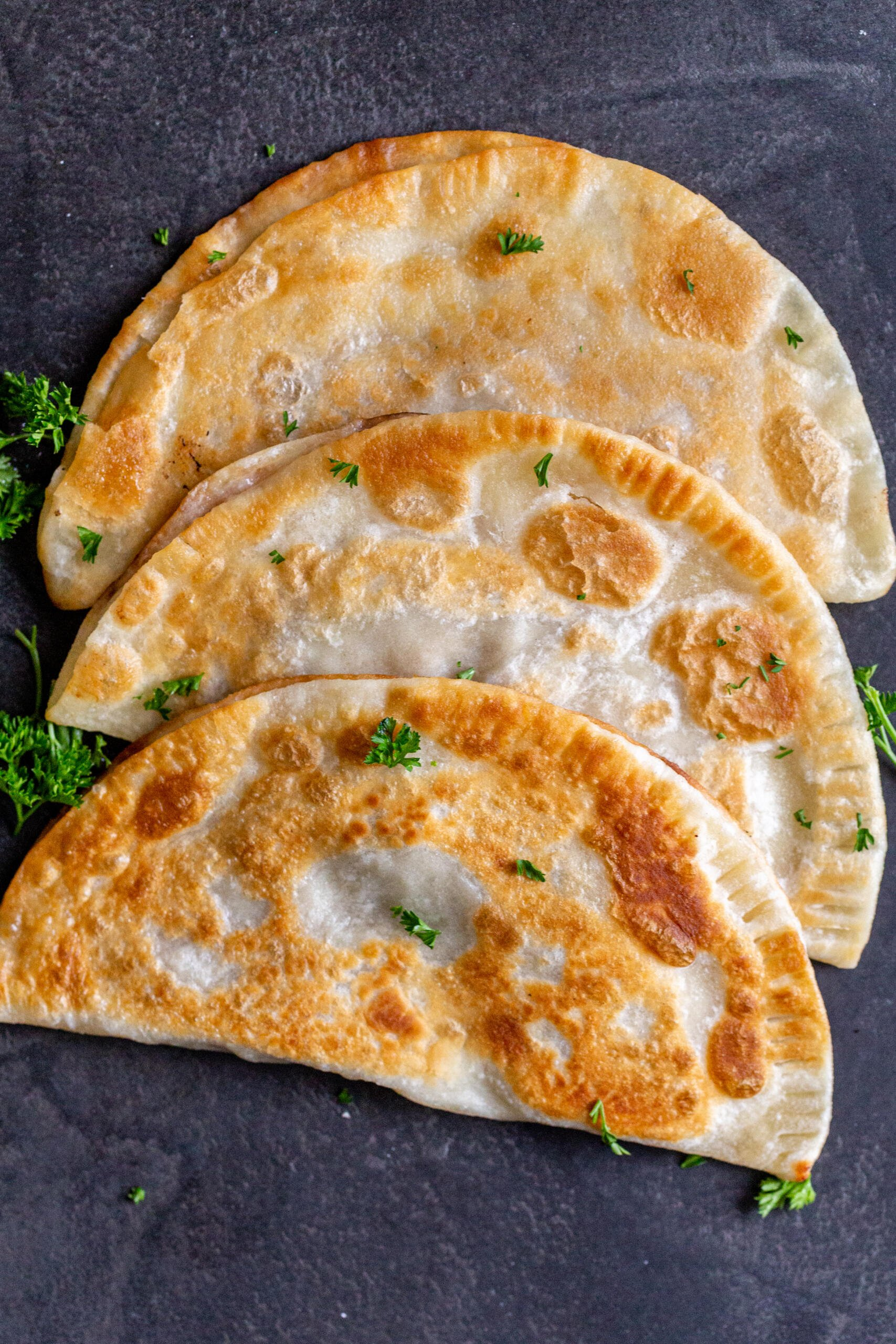 Chebureki with herbs on a counter