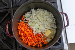 onion and carrots in a pot with butter cooking