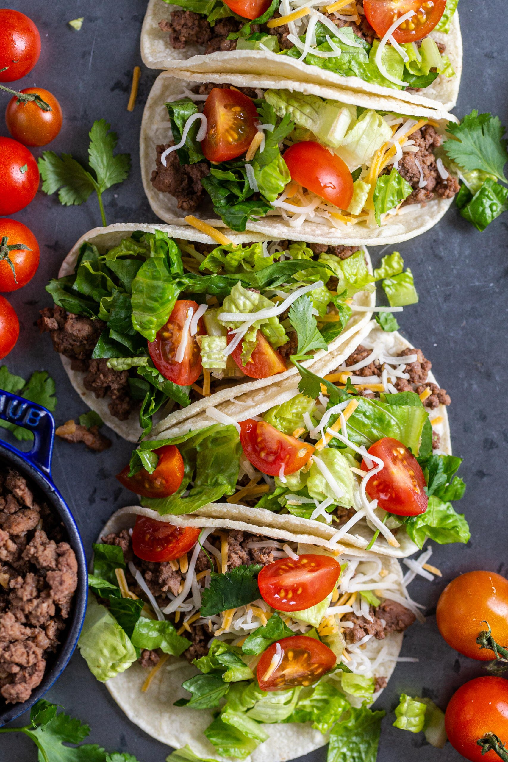 Ground beef tacos on a tray with veggies and meat on the sides