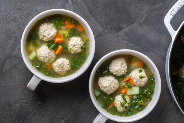 Two bowls of kale meatball soup