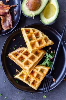 prepared chaffles on a plate with herbs and bacon