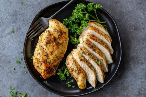 Chicken breast on a plate and one sliced into pieces
