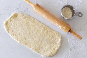 Rolled out flatbread dough with rolling pin next to it