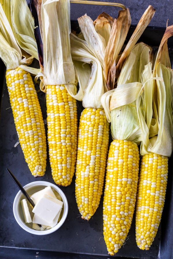 grilled corn on a tray with butter