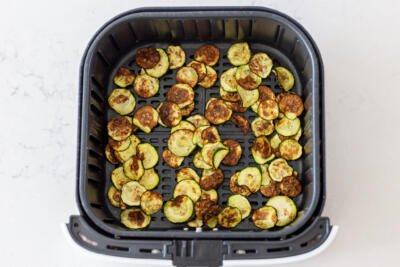 cooked zucchini in an air fryer basket