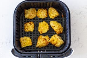 half cooked chicken nuggets in an air fryer basket
